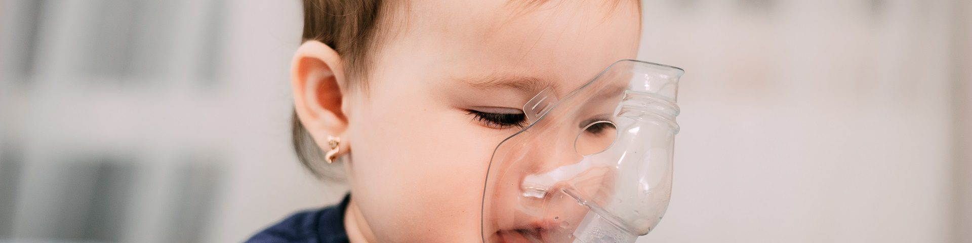 Baby girl using nebulizer to relieve cough